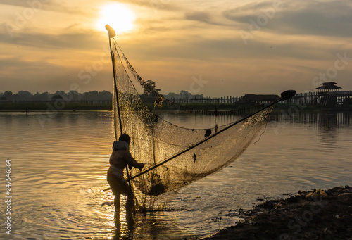 men fishing with triangular scoop net early morning at sunrise near iconic U-Bein Bridge, on shallow Lake Taungthamanin, Amarapura, Mandalay, Myanmar