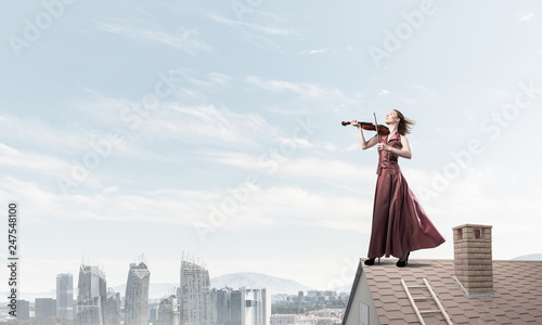 Woman violinist in red dress playing melody against cloudy sky. Mixed media