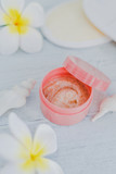 spa inspired set of scrub body lotions surrounded by flowers and seashells on light colored wood