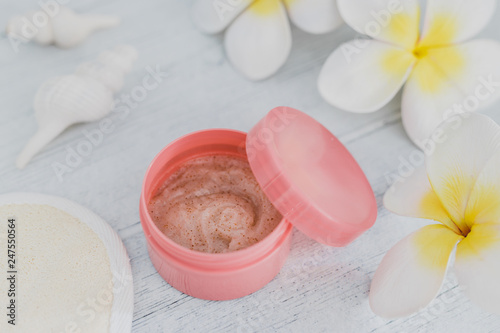 spa inspired set of scrub body lotions surrounded by flowers and seashells on light colored wood - 247550564