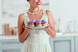 Partial view of pin up girl holding plate of cupcakes - 247564382