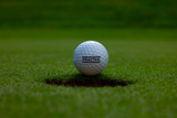 Golf Ball on the Border to the Golf Hole with Text Practice in Switzerland.
