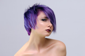 A beautiful, sexy girl with purple hair and a short haircut sits in the middle of the photo with a white background © Вячеслав Чичаев