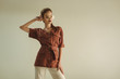 attractive fashionable woman in vintage clothing posing isolated on beige