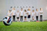 Kids stand in the line on a football field. Football ball on the foreground