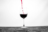 Red wine in the glass splashes in motion on a white background. Stylish design card