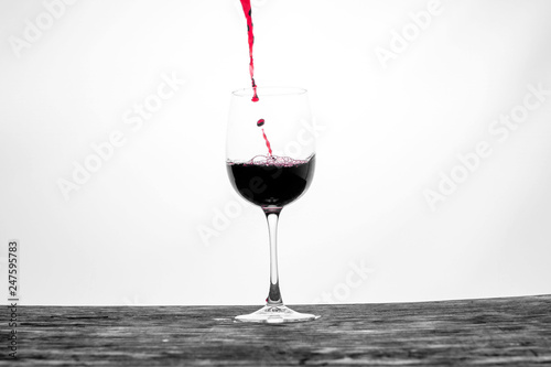 Red wine in the glass splashes in motion on a white background. Stylish design card - 247595783