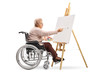 Quadro Elderly disabled woman sitting in a wheelchair and painting on a canvas