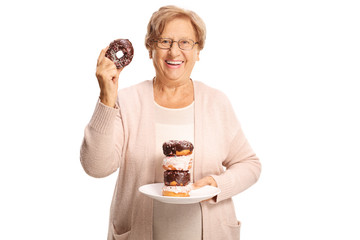 Cheerful elderly woman holding a plate of doughnuts in one hand and one doughnut in the other hand