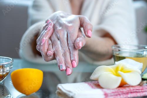 Woman applying the cream on her hands moisturizing them with natural cosmetics. Hygiene and care for the skin - 247599722