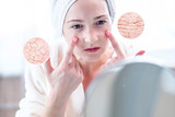 Woman looking at her dry skin with cracks and with first wrinkles. Circles increase the skin like a magnifying magnifier - 247600139