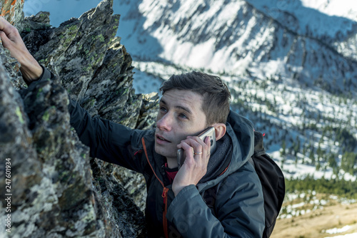 Man climbing the mountain to the top and talking on the phone. Communications and goal achievement in career