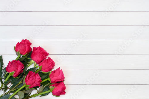 Bouquet of red roses on white wooden background. Top view, copy space