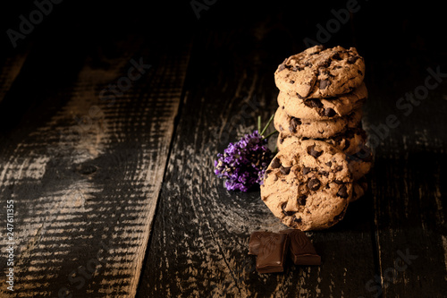 Column of cookies with chocolate bars in background of old black planks. - 247611355