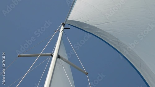 View directly upwards of mast and sail of yacht gently sailing under blue skies