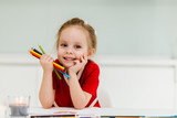 Cute little Caucasian girl in casual red dress draws and  sits at the table and holds colored pencils in his hands. Pozing amd making funny faces. Preparing a preschooler for school