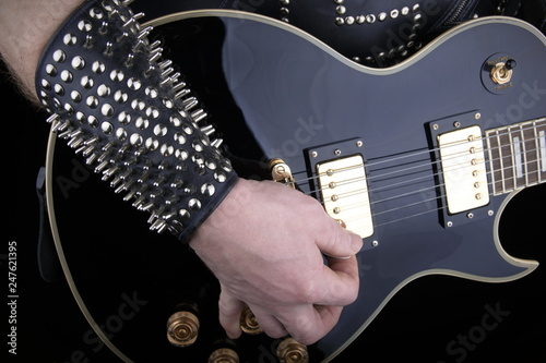 Guitarist.Closeup of electrical guitar fingerboard.Hand of rocker in leather  bracelet.Rock & roll, heavy metal,gothic,punk,horns sign and fist.Hard style.Rivets accessories - 247621395