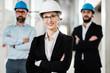 Leinwanddruck Bild - Engineers in hardhats posing in new building