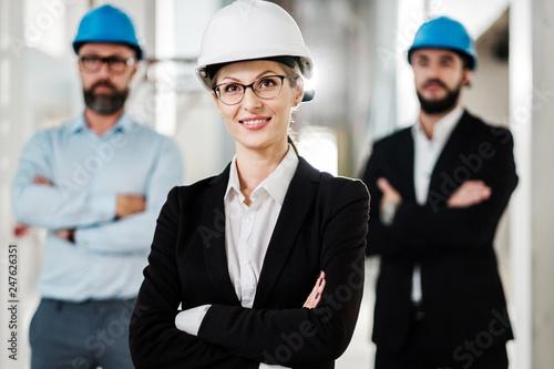 Leinwanddruck Bild Engineers in hardhats posing in new building