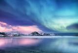 Aurora borealis na Lofotach w Norwegii. Zielone zorza polarna nad oceanem. Nocne niebo z polarnymi światłami. Nocy zimy krajobraz z zorzą i odbiciem na wodnej powierzchni. Obraz Norwegii