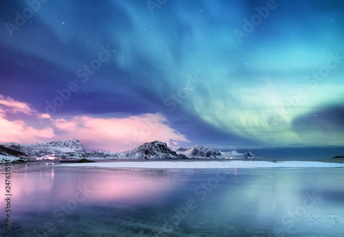 Leinwandbild Motiv Aurora borealis on the Lofoten islands, Norway. Green northern lights above ocean. Night sky with polar lights. Night winter landscape with aurora and reflection on the water surface. Norway-image