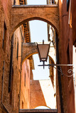 Siena, Italy narrow alley street in historic medieval old town village in Tuscany with nobody and arch passage looking up during day with lantern