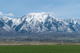 Snow capped mountains and green fields in Utah