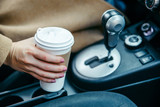 woman hand taking cup with coffee in car. close up. crop
