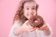 Portrait of a little smiling girl with donuts