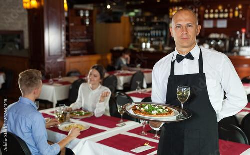Leinwandbild Motiv Waiter with serving tray meeting guests