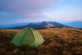 Green tent in spring mountains. Amazing evening highland. Landscape photography