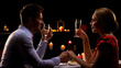 Leinwanddruck Bild - Man and lady holding hands and drinking champagne, romantic dinner in restaurant