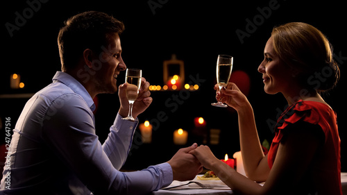 Leinwanddruck Bild Man and lady holding hands and drinking champagne, romantic dinner in restaurant