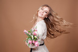 Happy beautiful elegant woman with pink bouquet of tulips over beige background. Copy space