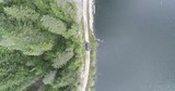 AERIAL: Birdseye view of a truck driving down dirt road beside a lake.