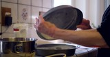 A woman chef coating round baking pans with flour to prevent sticking as she bakes vegan chocolate cake for dessert in a kitchen. - 247686971
