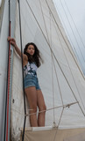 young teen girl standing on the boom of a saillboat - 247690573