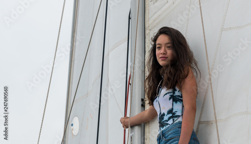 young teen girl standing on the boom of a saillboat