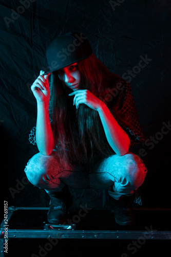Beautiful high fashion model in bright neon blue and red lights posing in a studio sitting on a black background - 247691157