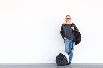 Fashionable young woman standing and waiting against plain white wall on the station whit travel bag by her side. Copy space on white wall.