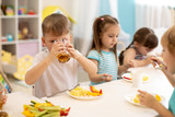 Lunch in daycare. Group of children eat healthy food. Kid boy drinking juice during dinner in kindergarten - 247696116