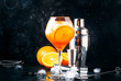 Leinwanddruck Bild - Aperol spritz cocktail in big wine glass, summer Italian low alcohol cold drink, dark bar counter background with tools, summer mood concept, selective focus