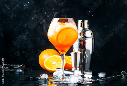 Leinwanddruck Bild Aperol spritz cocktail in big wine glass, summer Italian low alcohol cold drink, dark bar counter background with tools, summer mood concept, selective focus