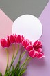Tulips flowers. Flower frame. Flower card. Pink tulips and white round frame on a  pink lilac gray background.Mothers Day. International Women's Day. top view,copy space.