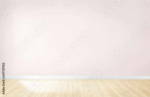 Light pink wall in an empty room with a wooden floor - 247707952