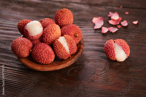 Foto Murales Fresh lychees close up on wooden background