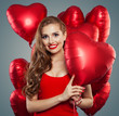 Leinwandbild Motiv Happy woman holding balloons red heart. Surprise, valentines people and Valentine's day concept. Red lips makeup. Positive emotion.