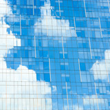 Blue sky and white clouds reflection on glass facade of a modern office building - 247719326