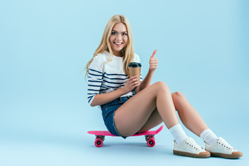 Cheerful girl with cup of coffee sitting on skateboard and showing thumb up on blue background