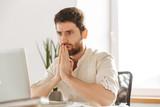 Image closeup of tense businessman 30s wearing white shirt using laptop, while working in modern office - 247734932